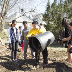 Middle schoolers spread compost on the garden.