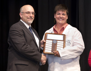 Dr. Scott Dalrymple, president of Columbia College (left) presents Melanie Dollens with the Nursing Program award for Clinical Excellence at the May 2014 pinning ceremony.