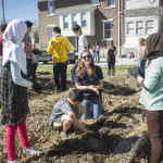 International Student Advisor Leah Buretta guides the middle school students in tending to the garden.