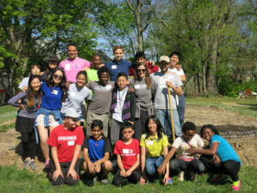 International Club and Jefferson Middle School ELL students pose in front of the Cougarden after harvesting spinach.