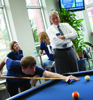 Always involved in campus activities, Dr. Smith regularly plays pool with students in Atkins-Holman Student Commons.