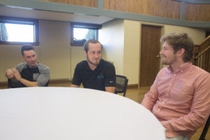 From left, alumni Michael Hudelson '10 and Zach Oppland '14 talk with senior Garrett Waage at the Computer and Mathematical Sciences department networking lunch in Dorsey Gym. (Photo by Kaci Smart)