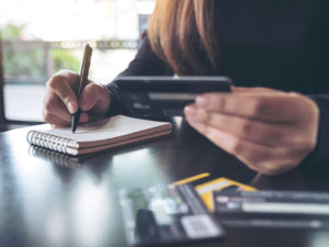 Closeup image of a woman holding a credit card while writing down on notebook on table