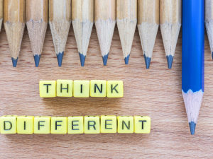 """Think Different"" motivational slogan on wooden table with group of pencils."