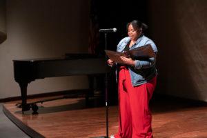 Ty Monroe reading poem on stage