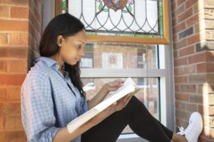 Woman studying in front of a stained-glass window