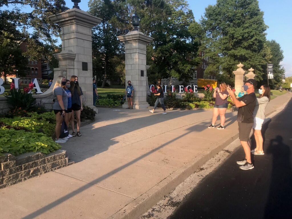Family taking picture of female students at Rogers Gate during sunset