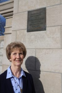 Genie Rogers under the plaque honoring JK Rogers at Rogers Gate