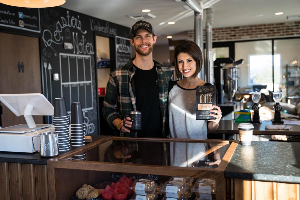 Man and woman standing behind counter of a coffee shop, holding a mug and bag of coffee beans
