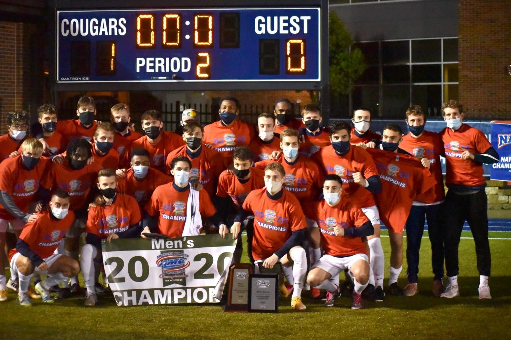 The CC men's soccer team poses in front of the scoreboard with the 2020 AMC Championship banner and trophies. The players are wearing masks.