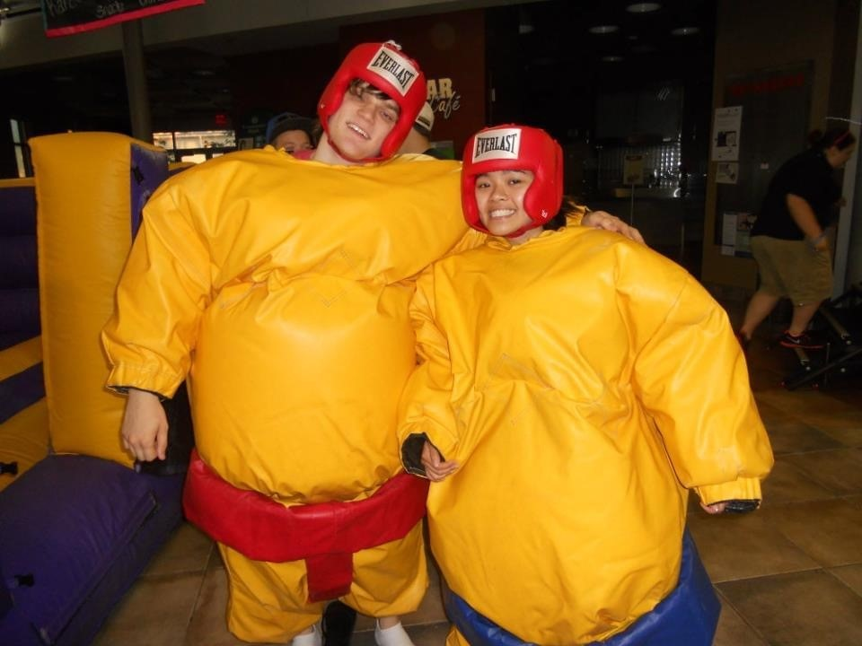 Man and woman in exxageratedly large rubber sumo wrestling suits