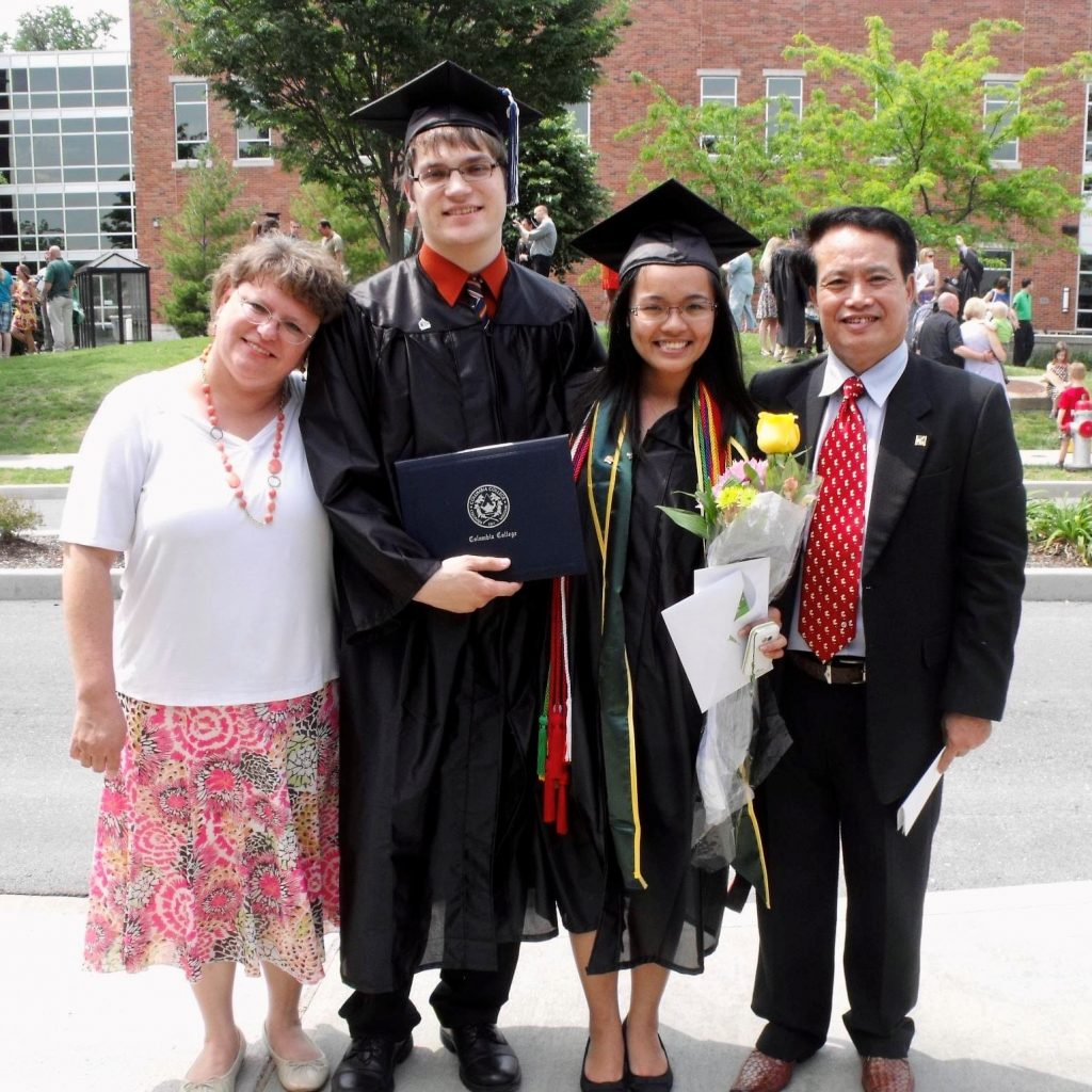 A male and female college graduate each flanked by their parents outside