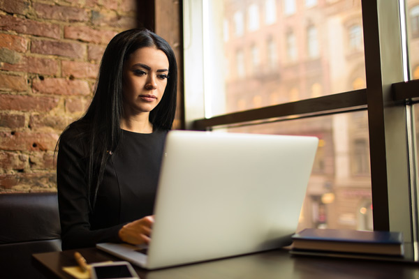Woman with long, dark hair working on her laptop in front of a window.