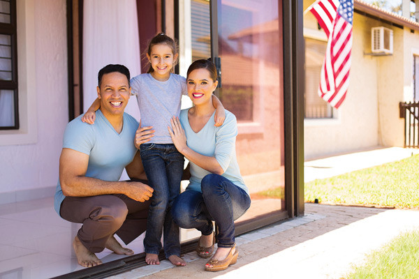 Family of three standing on the patio outside their house. There is an American flag in the background.