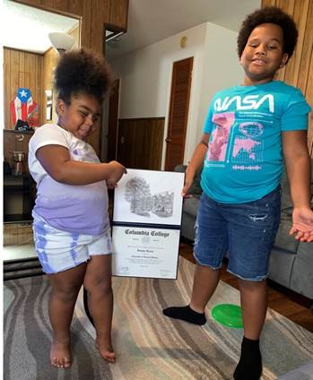 image of two children holding their mother's diploma in their living room. Both children are bearming.